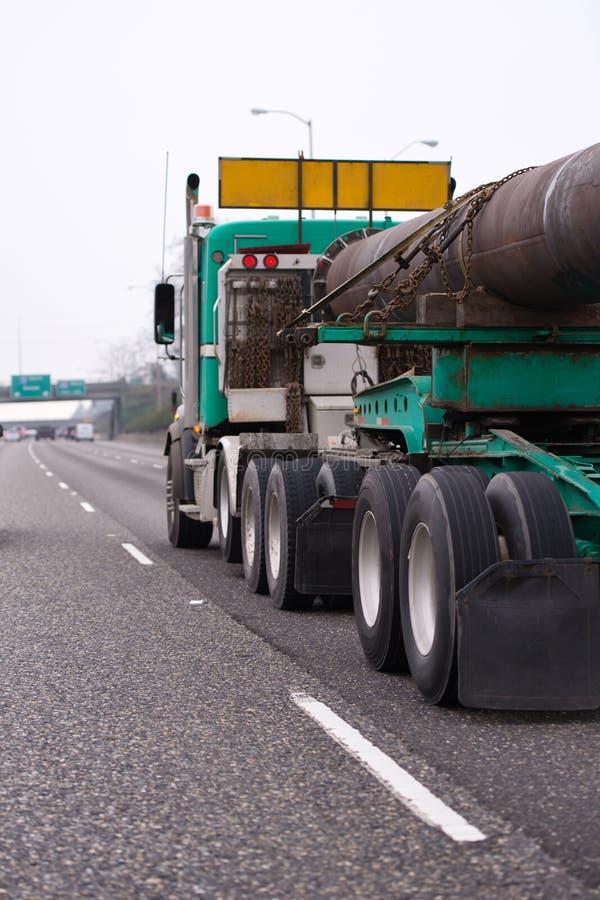 Großer der Anlage LKW halb, der Überformatrohrfracht auf dem strai transportiert stockbild
