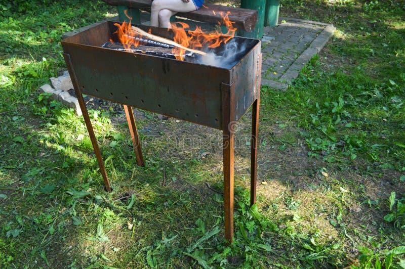 Großer Eisengusseisen-Metallmessingarbeiter für Grillgrill-Picknickkebabs mit dem hölzernen Brennen meldet ein Feuer mit den Zung stockbilder