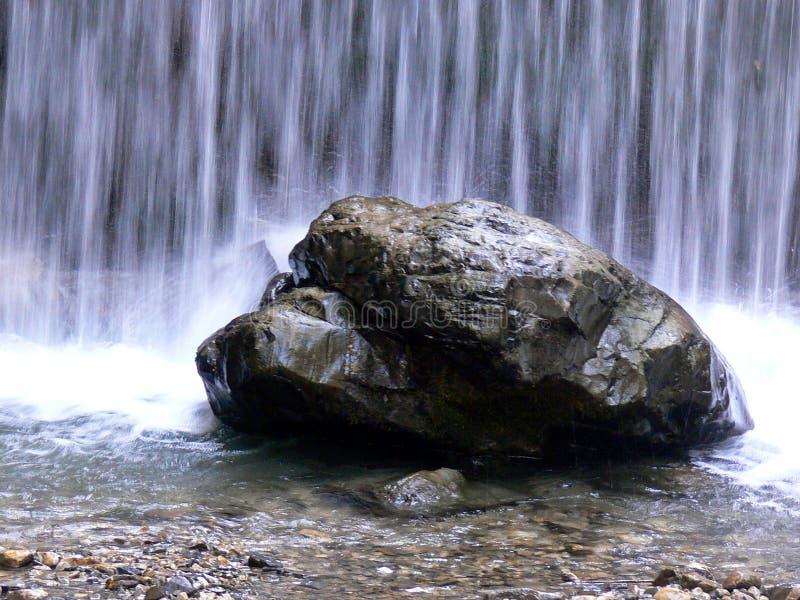 Großer Flussstein im Fluss vor einem Wasserfall stockbild