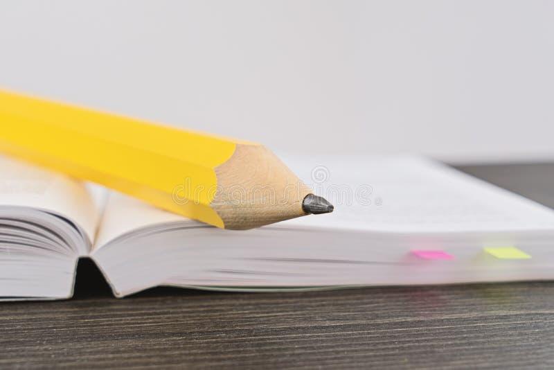 Großer gelber Bleistift auf einem offenen Buch stockbilder