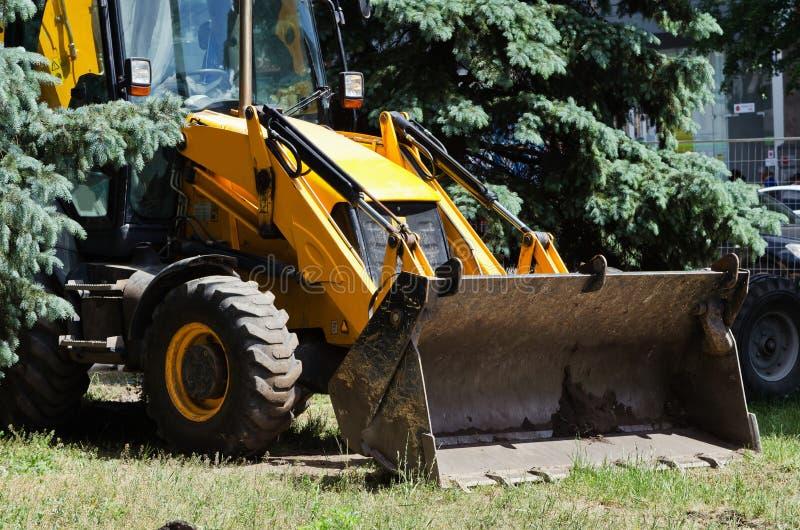 Großer gelber Traktor mit einem Eimer stockfotografie