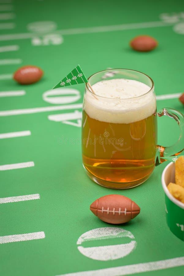 Großer Glasbecher kaltes Bier auf Tabelle mit superbowl Parteidekor stockbild