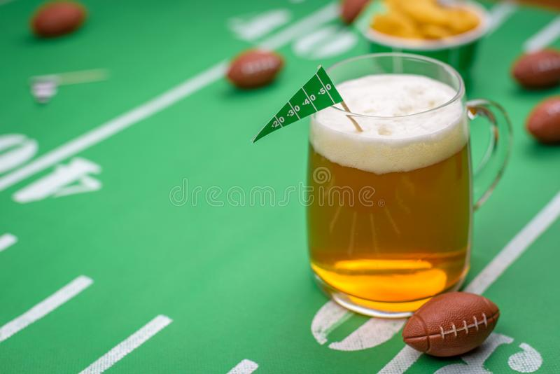 Großer Glasbecher kaltes Bier auf Tabelle mit superbowl Parteidekor stockfotos