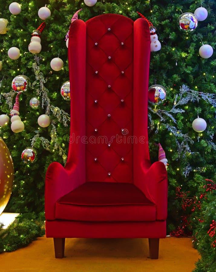 Großer hoher Stuhl für Santa Claus mit grünem Weihnachtsbaum im Hintergrund stockfotografie