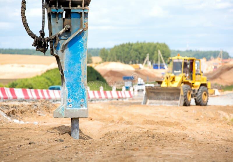 Großer Jackhammer, der den Asphalt pflastert während der Straßenbauarbeiten zerquetscht stockfoto