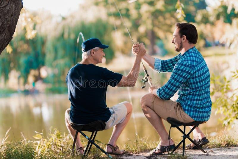 Großer Job Vater- und Erwachsensohnfischen auf der Flussbank, Sitzen auf den Klappstühlen, die ihre Rückseite auf der Kamera dreh lizenzfreie stockbilder