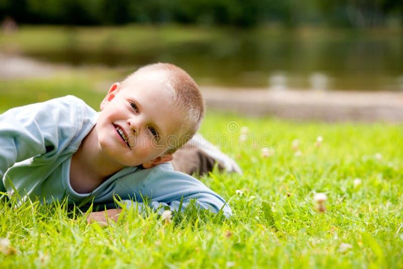 Großer Junge rollt über dem Gras lizenzfreie stockfotos