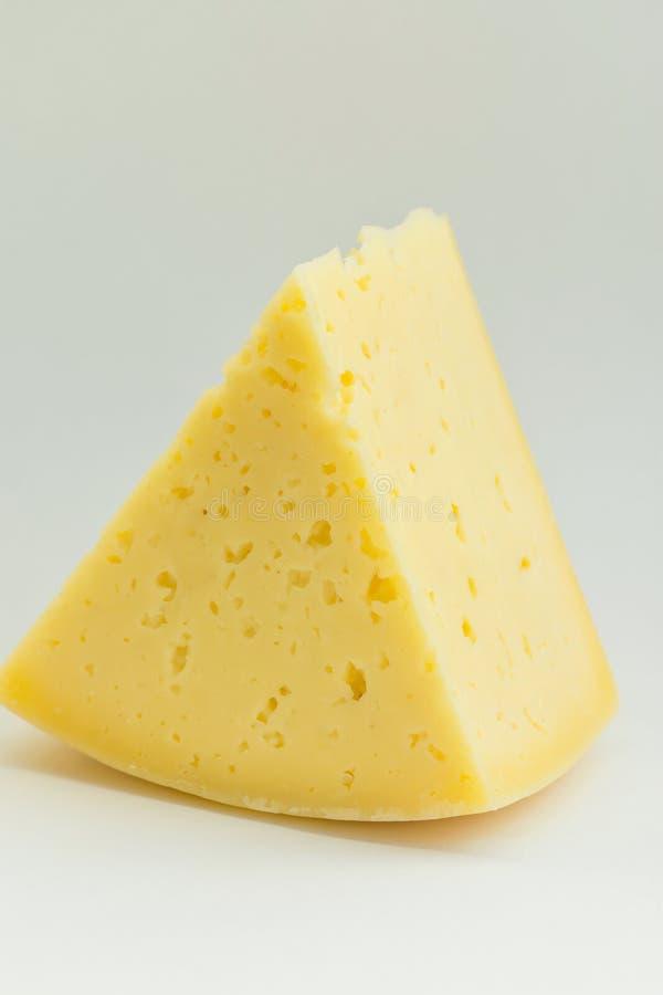Großer Klumpen-Keil des alpinen sahnigen appetitanregenden hellgelben Tilsiter-Käses auf weißem Hintergrund Beschaffenheit mit Sp stockfotografie