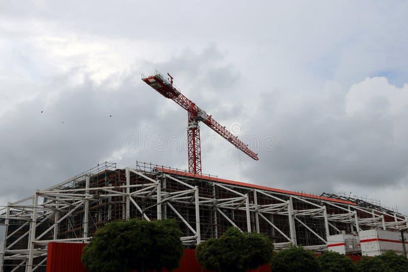 Großer Kran über dem Bau des Gebäudes auf Wolken- und Himmelhintergrund stockbild