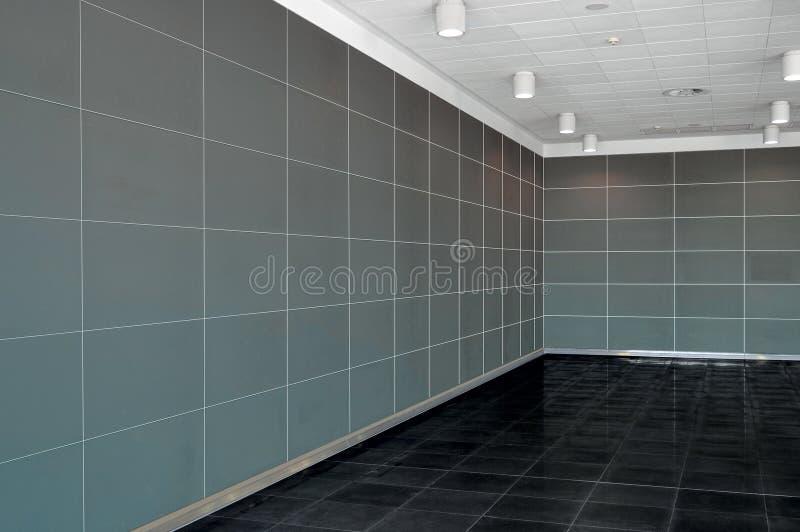 Großer leerer Rauminnenraum mit dunkelgrauer Wand, whire Decke und d lizenzfreie stockbilder