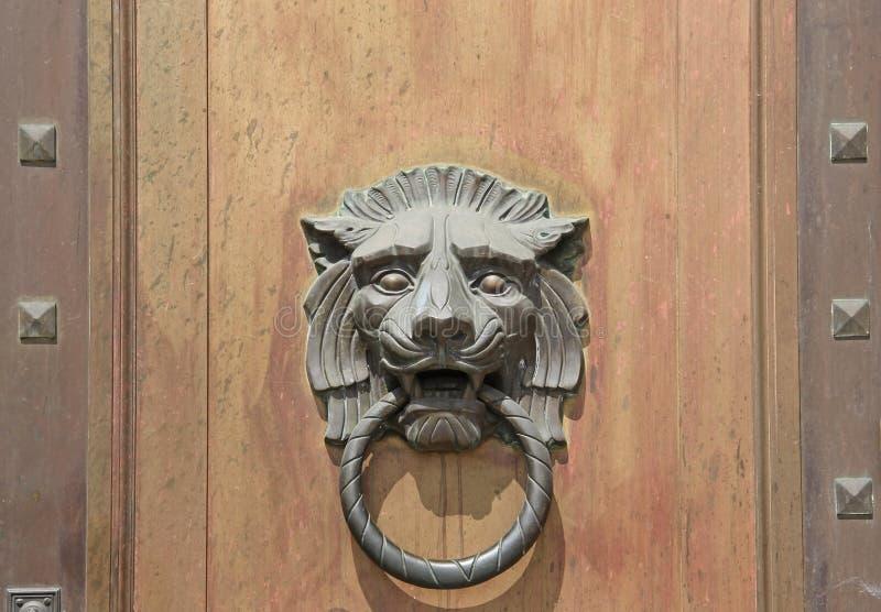 Großer Lion Head Door Knocker auf hölzernem Tür-Hintergrund stockbild