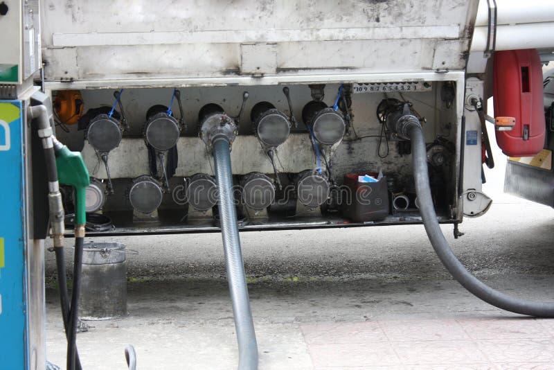 Großer LKW bespritzt für Brennstoffstation, Pumpen und Ölbarrel mit einem Schlauch stockfotos