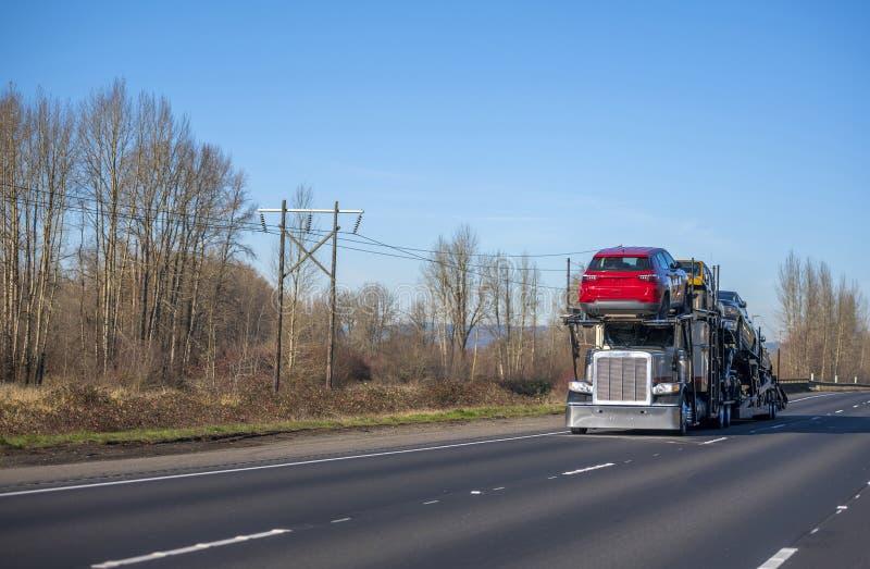 Großer LKW des Anlagenauto-Schleppers halb, der halb Autos auf Anhänger transportiert und auf Herbststraße mit bloßen Bäumen fähr lizenzfreie stockfotografie