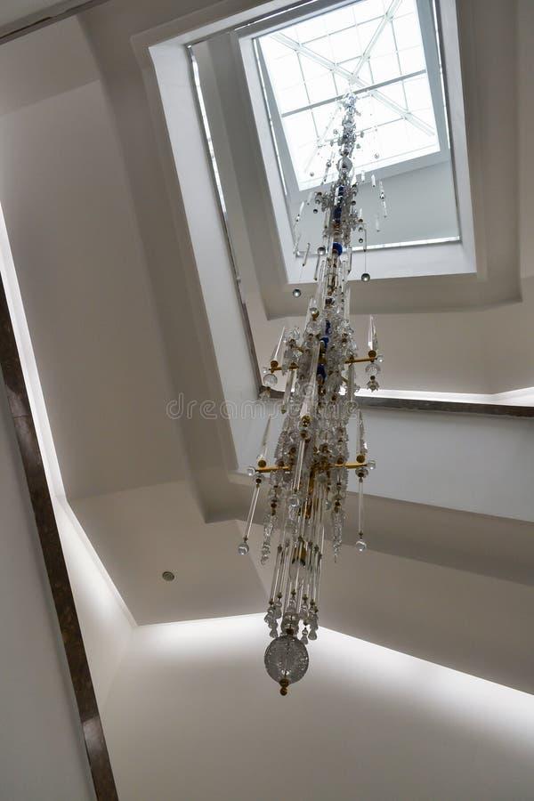 Großer moderner Leuchter zum Belichten die gewundene Treppe mit einer Höhe einiger Böden lizenzfreies stockfoto