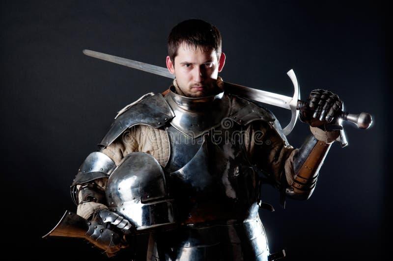 Großer Ritter, der seine Klinge und Sturzhelm anhält lizenzfreies stockfoto