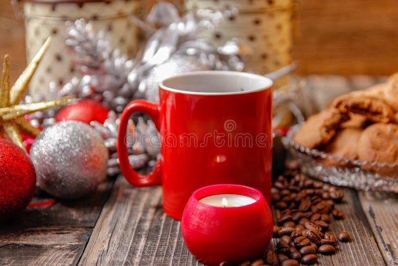 Großer roter Tasse Kaffee, Plätzchen gefüllt mit Schokolade, Weihnachtsbällen, Kerzen und Kaffeebohnen stockbild