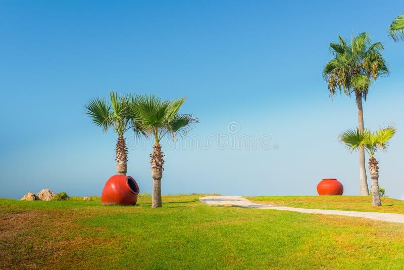 Großer roter Vase im grünen Park mit Palmen stockfotografie