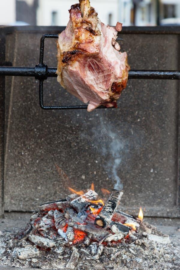 Großer saftiger Schweinbraten auf Bratenwender mit Kohle und Rauch in Prag Traditionelle tschechische Küche stockfotografie