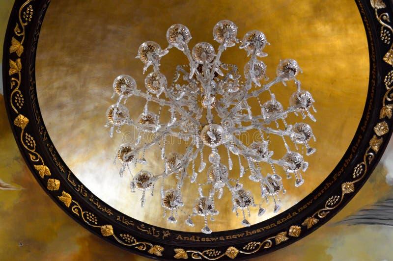 Großer schöner luxuriöser Kristallglasleuchter mit Anhängern und Verzierungen und ein Rahmen von Gold-Verzierungen auf dem hohen  lizenzfreie stockfotografie