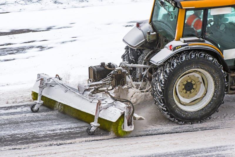 Großer Schnee, der Traktormaschine bei der Arbeit über die Straße während eines Schneesturms im Winter pflügt stockbild