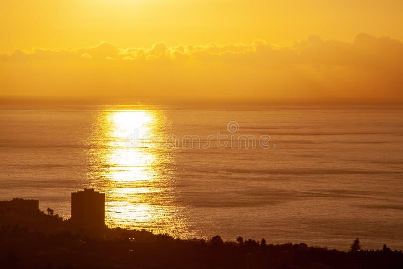 Großer Sonnenuntergang durch das Meer mit Wolken stockfoto