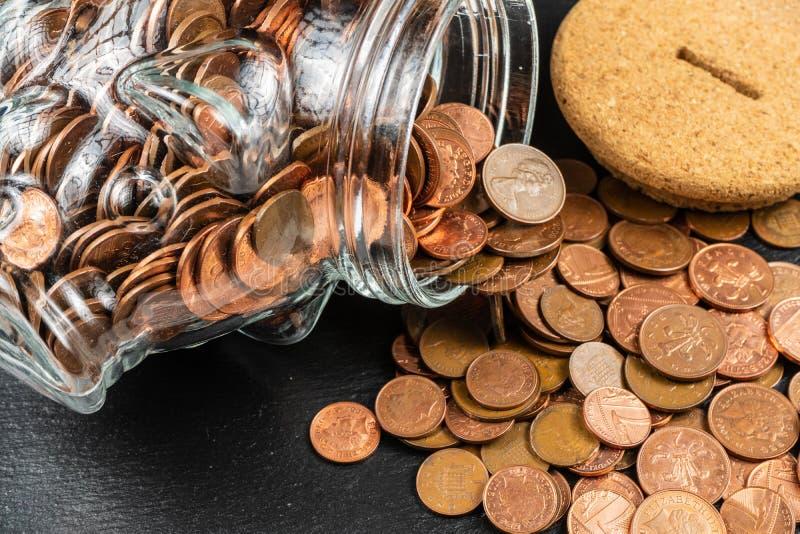 Großer Sparschwein-Geld-Kasten, Glasgeld-Glas mit britischen Münzen stockfoto