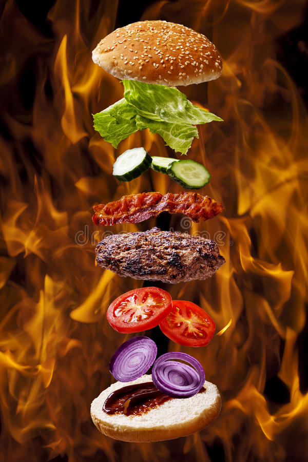 Großer Speckgrillburger auf Feuerflammengrill lizenzfreie stockfotografie