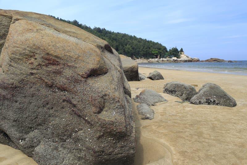 Großer Stein auf sandigem Strand stockbild