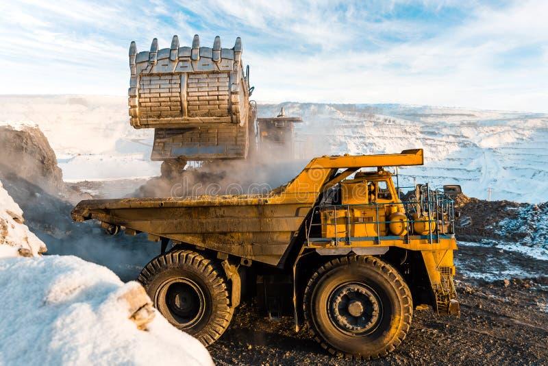 Großer Steinbruchkipplaster Laden des Felsens im Kipper Ladenkohle in Körper-LKW Nützliche Mineralien der Produktion bergbau stockfotos