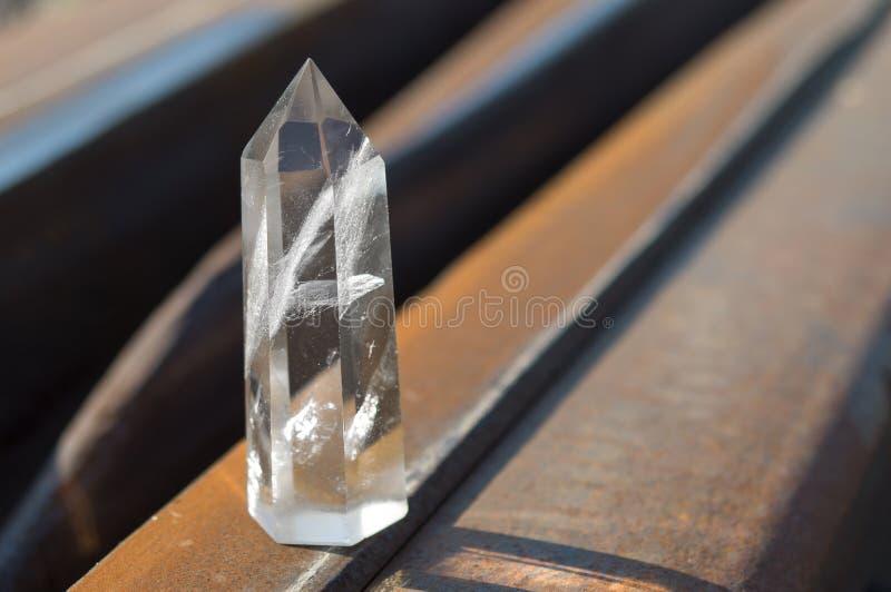 Großer transparenter mystischer facettierter Kristall des weißen Quarzes auf Schienen auf industrieller Hintergrundnahaufnahme Ei lizenzfreies stockbild