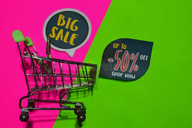 Großer Verkauf und bis -50% weg vom Geschäfts-jetzt Text und dem Einkaufswagen stockbild