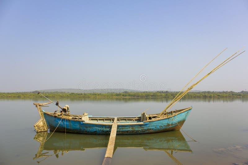 großes altes Fischerboot mit einem Motor und Angeln verankerte mit einer Leiter am Ufer gegen den Hintergrund von einem Fluss und lizenzfreies stockbild
