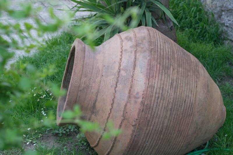 Großes antikes Tongefäß oder traditionelles Glas auf verlassener Hütte Altgriechischer Amphora stockbild