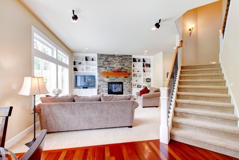 Großes beige Luxuxwohnzimmer mit Treppenhaus. lizenzfreies stockfoto