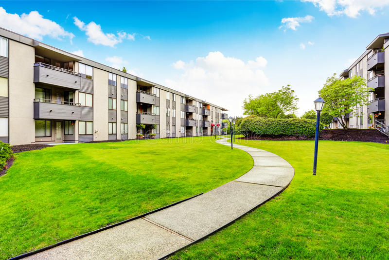 Großes beige Wohngebäude mit drei Böden und Balkonen Gut unterhaltener Rasen stockbilder