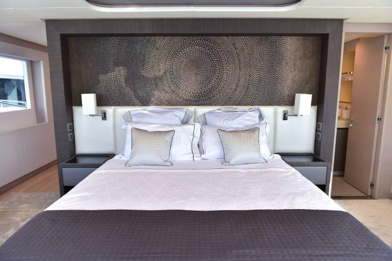 Großes Bett innerhalb des Bootes mit vielen Kissen und Toilette und kleine Tür und Fenster stockbilder