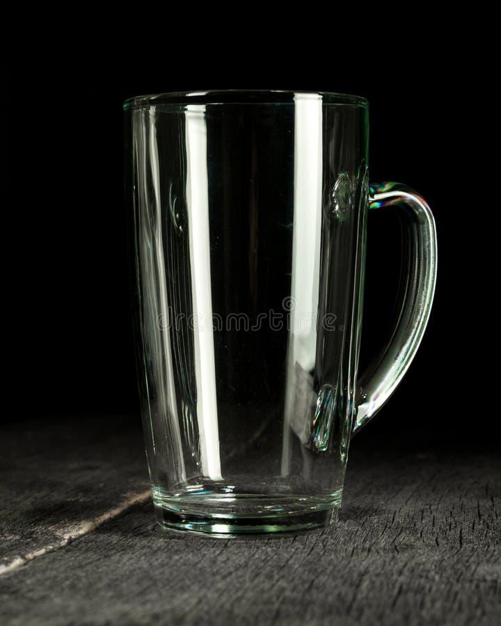 Großes Bierglas mit weißem transparentem Glasgriff Dunkler hölzerner Hintergrund stockbild
