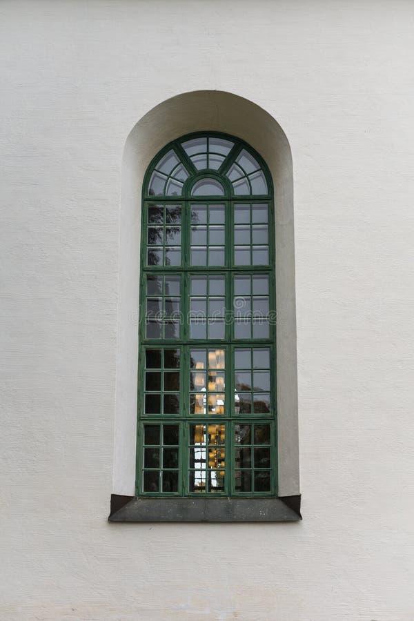 Großes Bogenfenster von einer weißen Steinkirche stockfotografie