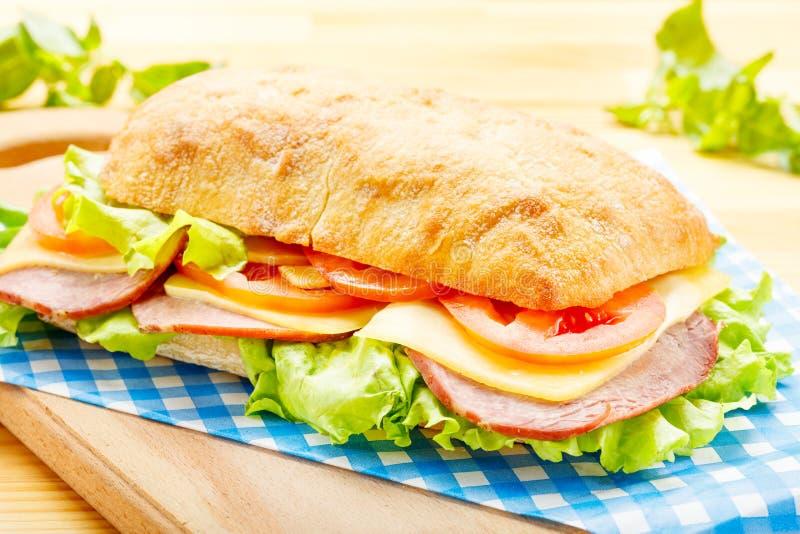 Großes Ciabatta-Sandwich mit Speck, Kopfsalat, Tomate, Käse lizenzfreies stockfoto