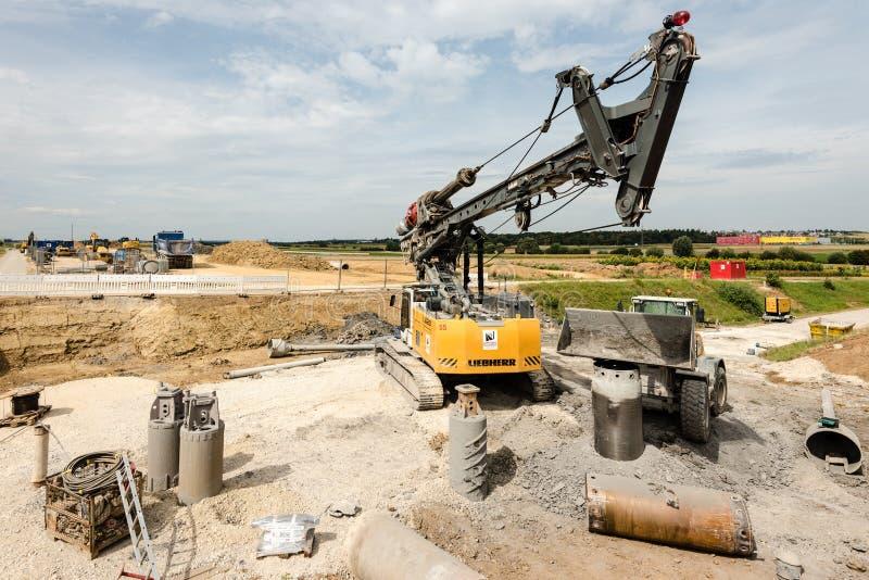 Großes Drehbohrgerät und Bagger auf Baustelle stockbilder