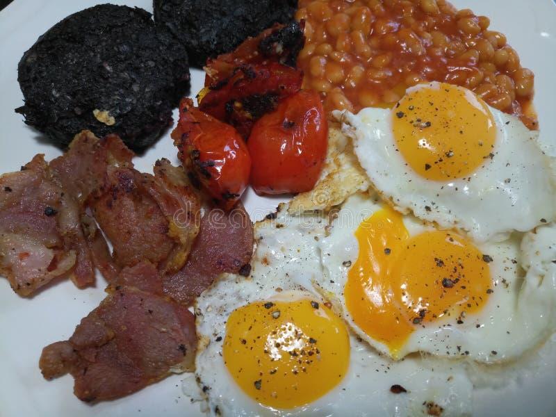 Großes englisches Frühstück mit drei Eiern, knusperigem Speck und Bohnen stockfoto
