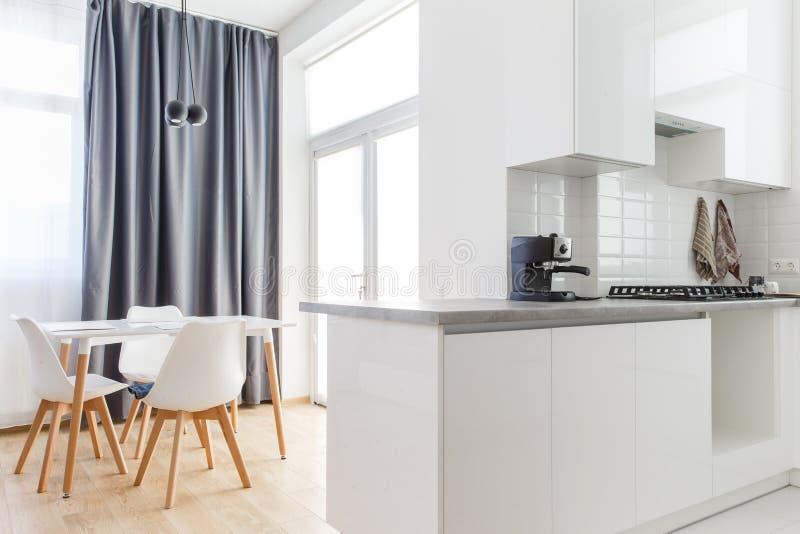 Großes Esszimmer mit der Küchenwand auf der rechten Seite und der Tabelle mit den Stühlen auf der linken Seite lizenzfreies stockfoto