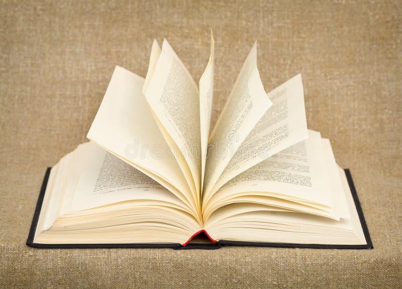 Großes geöffnetes altes Buch, das gegen ein raues Segeltuch liegt stockfotos