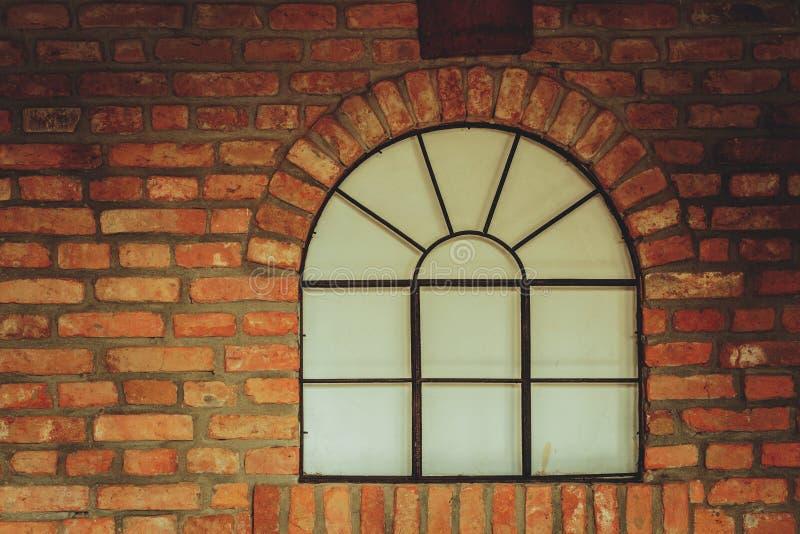 Großes gerundetes Fenster auf Wand des roten Backsteins stockfotografie