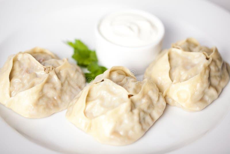 Großes großes enormes der Manti-Mehlkloß-Ravioli mit Sauerrahm und Petersilie auf einem Plattenmenü für das Caférestaurant-Weiß b stockfoto