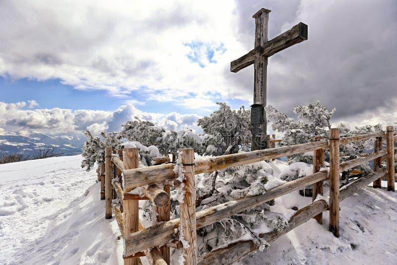 Großes hölzernes Kreuz auf der Bergspitze mit dem hölzernen Fechten stockbilder