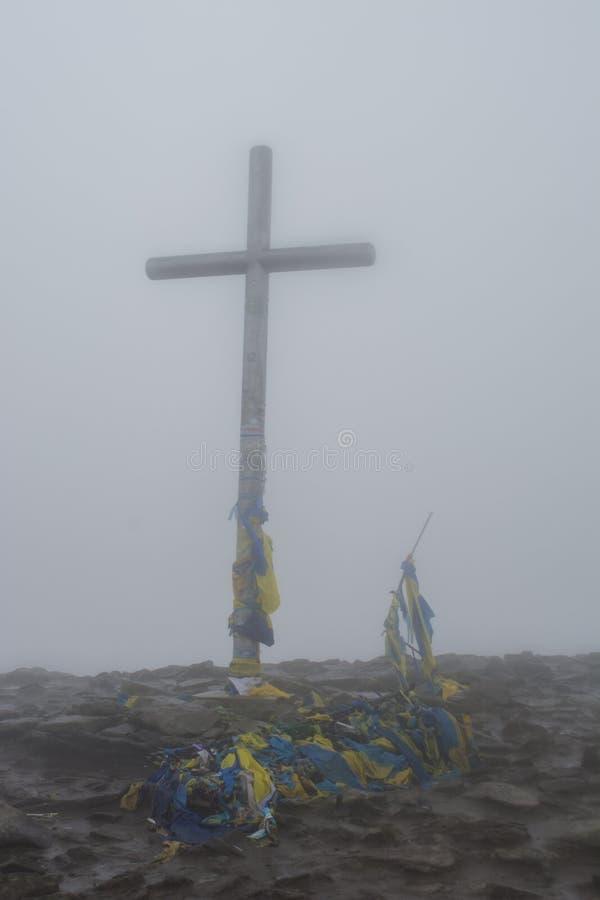 Großes hölzernes Kreuz umfasst mit Flaggen von Ukraine lizenzfreie stockbilder