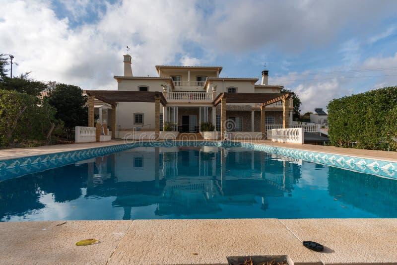 Großes Haus mit Swimmingpool an einem bewölkten Tag lizenzfreies stockbild