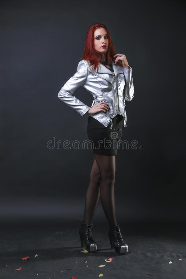 Großes herrliches rotes Hauptmädchen, das in einer silbernen Motorradjacke im Studio aufwirft lizenzfreie stockbilder