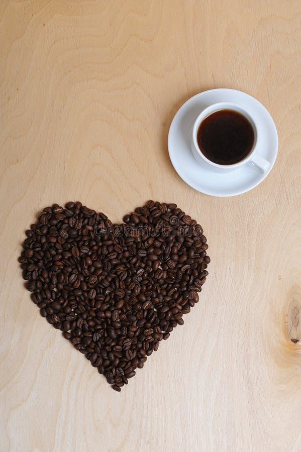 Großes Herz gemacht von den Kaffeebohnen und von einem Tasse Kaffee auf einem hellen hölzernen Hintergrund, Draufsicht stockbilder